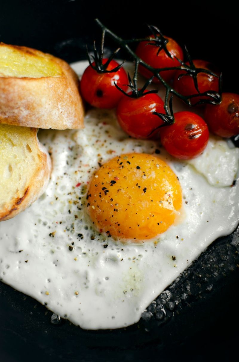 plate with cooked egg and tomatoes